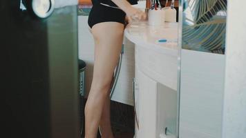 giovane ragazza bruna in top nero guardando nello specchio in bagno. toccare i capelli