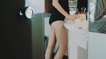 giovane ragazza bruna in top nero guardando nello specchio in bagno. toccare il viso, le labbra