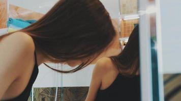 giovane ragazza bruna spazzolare i denti davanti allo specchio in bagno. Lavello. Sorridi