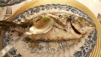 versando salsa e olio sul pesce appena grigliato