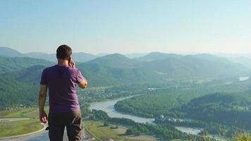 retrato de homem falando em um telefone celular em uma paisagem de fundo de montanha, altai, rússia video