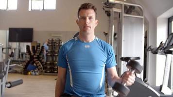 Hombre practicando flexiones de bíceps con pesas en un gimnasio, vista frontal
