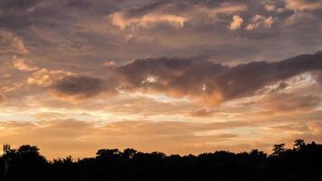 Déplacement de nuages sur un bloc de construction et des arbres timelapse (silhouette)