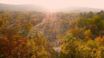 4k aérea: estrada de terra em terreno baldio, pôr do sol, outono
