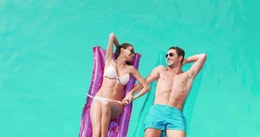 couple détendu avec des lunettes de soleil sur lilo