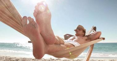 homem relaxando em uma rede na praia video