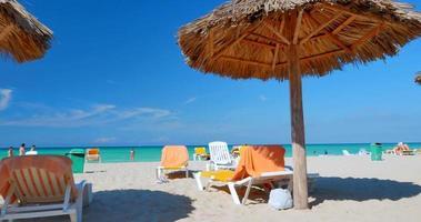 Touristen entspannen am tropischen Strand unter Strohschirm Palapas.
