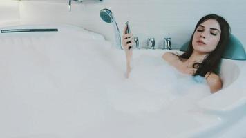 menina morena desfrutar de um banho cheio de espuma. toque no smartphone. relaxar. em repouso