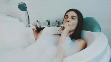 ragazza fuma sigaretta elettronica nella vasca da bagno piena di schiuma. bere vino rosso. rilassante