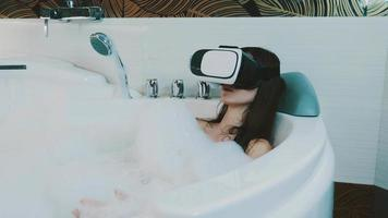 Girl relax in bath full of foam in bathroom with virtual reality glasses on head