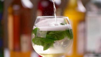 Flasche gießt Getränk in Weinglas.