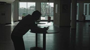 figuren av en ung man som lutar sig på ett bord i lobbyn i rummet och håller en telefon video