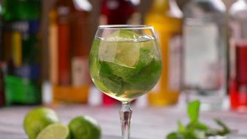Tongs put lime into beverage.