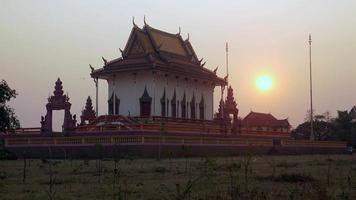 casal de rapazes andando de bicicleta em frente a um cercado de pagode ao pôr do sol