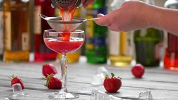 rotes Getränk gießt durch Sieb.