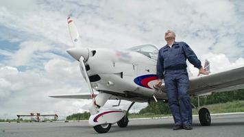 piloto maduro de óculos escuros em pé diante do avião