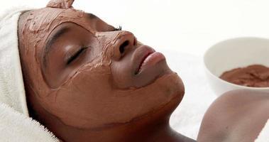 massagista aplicando produto no rosto do cliente