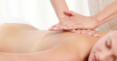 massaggiatrice che massaggia la schiena del suo cliente