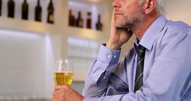 uomo d'affari preoccupato che beve una birra dopo il lavoro