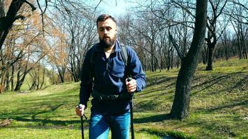 jeune randonneur avec un sac à dos et des bâtons de randonnée se promène en plein air