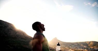 atleta afroamericano che spruzza acqua sul viso dopo l'esercizio