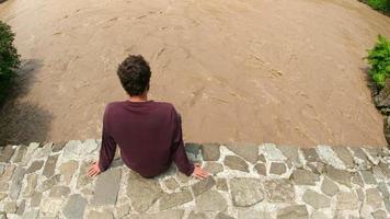Hombre sentado superior histórico puente de arco sobre el río corriente de agua