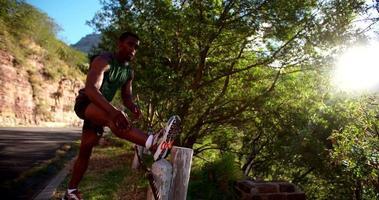 Corredor afroamericano masajeando sus músculos durante el ejercicio al aire libre