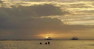 Kinder spielen im Wasser bei Sonnenuntergang