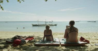 duas meninas tomando banho de sol na praia video