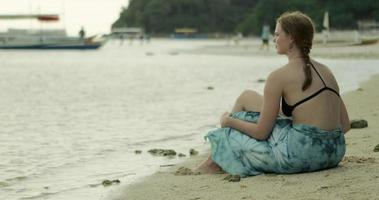 ragazza seduta sulla spiaggia video