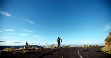 atleta correndo ao longo de uma estrada em câmera lenta video