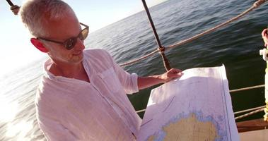 Mature traveler on sailing vessel looking at map and smiling