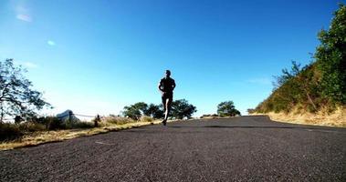 foto em câmera lenta do atleta correndo ao longo da estrada ao ar livre video