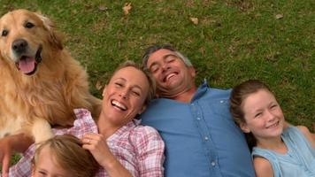 famiglia felice sorridendo alla telecamera con il loro cane