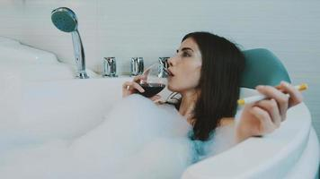Girl taking bath full of foam. Smoke electronic cigarette, drink red wine video