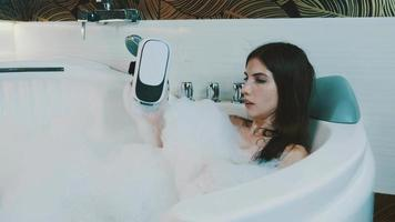 Girl take bath full of foam in bathroom put off virtual reality glasses. Device