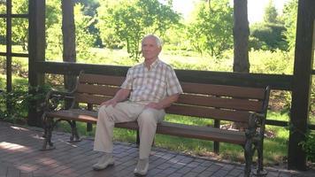 anciano sentado en un banco. video