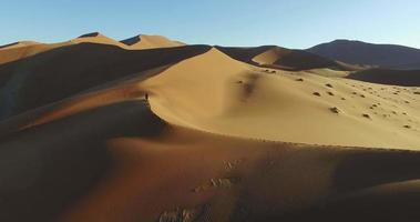 4K aerial view of male tourist walking over the sand dunes in the Namib desert inside the Namib-Naukluft National Park