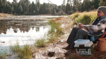 anziano uomo nero su un viaggio in campeggio pesca da un lago rurale video
