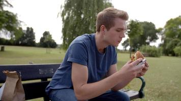 joven blanco sentado en un banco del parque disfrutando de una hamburguesa