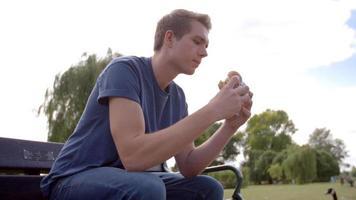 joven sentado en un banco del parque comiendo hamburguesas, ángulo bajo