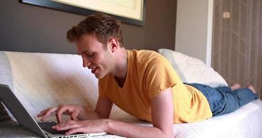 jeune homme, coucher lit, utilisation ordinateur portable