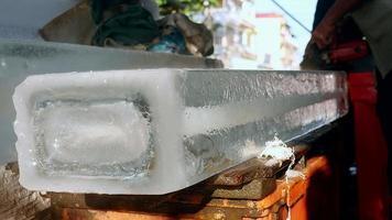 vendedor de hielo precortando pequeños bloques de hielo con una sierra circular