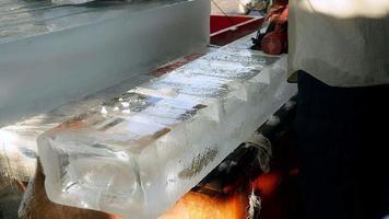 vendedor de hielo precortando pequeños bloques de hielo con sierra circular