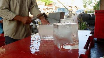 Vendedor de hielo dividiendo bloques de hielo con su hacha