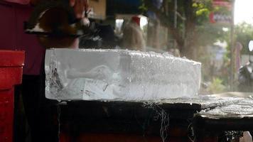 vendedor de gelo cortando pequenos blocos de gelo com uma serra circular