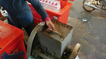 Vendedor de hielo triturando bloques de hielo con una trituradora