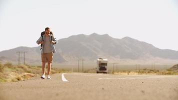 uomo in vacanza autostop lungo la strada di campagna girato su r3d video