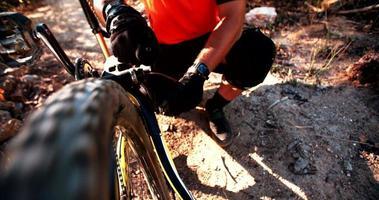 Mountainbiker repariert sein kaputtes Fahrrad auf einer Spur