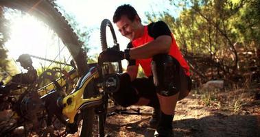 Mountainbiker repariert sein Fahrrad auf einer Spur